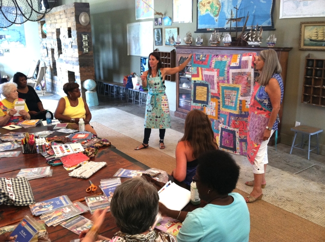 Carrie Bloomston (left) and Rhonda Greenberg (right) hold up a quilt made from fabrics designed by Bloomston during a Happy Flag Project workshop with Bib & Tucker Sew-Op.